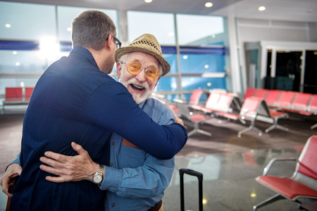 Happy moment. Portrait of pleased aged father in glasses and his grownup child are hugging each other while standing at airport lounge. Old man is looking at camera with glad. Copy space in right side 版權商用圖片