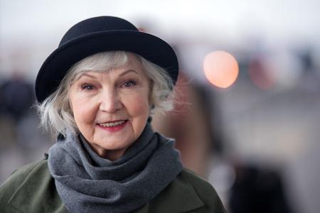 세 아름다움. 검은 모자에 쾌활 한 오래 된 여자의 초상화 미소로 카메라를 찾고있는 동안 거리에 서있다. 오른쪽에 공간 복사