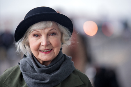Aged beauty. Portrait of cheerful old woman in black hat is standing on street while looking at camera with smile. Copy space in the right side