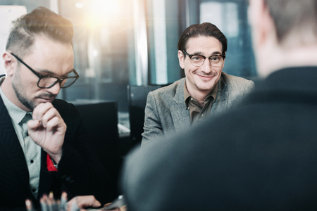 Portrait of cheerful male speaking with partner while locating at desk. Labor and conversation concept