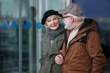 Feeling excitement. Elegant old woman is going under the handle with her husband. She is looking at him with happy smile while exiting from airport building. Copy space in the left side