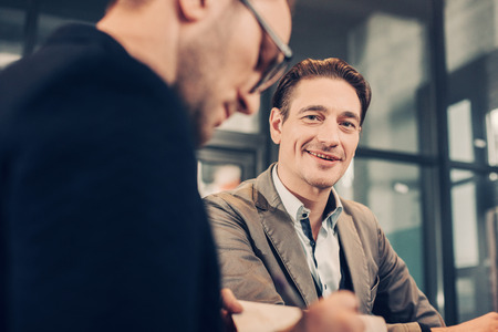 Low angle portrait of smiling businessman speaking with calm partner in office. Profession concept Imagens