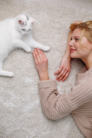 Top view of smiling lady lying on the floor and playing with animal. She is looking at pet and touching its paw Reklamní fotografie
