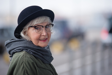 Pleasant lady. Portrait of charming stylish senior female in glasses is standing outside and looking at camera with slight smile. Copy space in the right side Foto de archivo