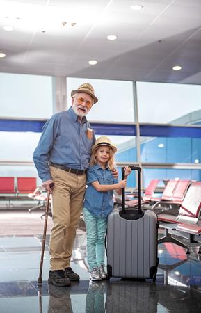 楽観的な白髪の祖父と彼の小さな孫娘の完全な長さの肖像画は、空港のラウンジで一緒に立っています。女の子がスーツケースを持っている間、彼