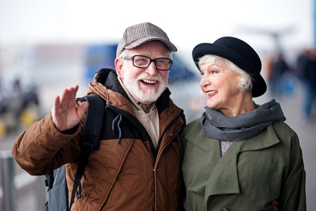 Always have fun. Delighted old couple is standing on street while smiling and gesturing positively. Man is hugging elegant woman while she is looking at him with joy