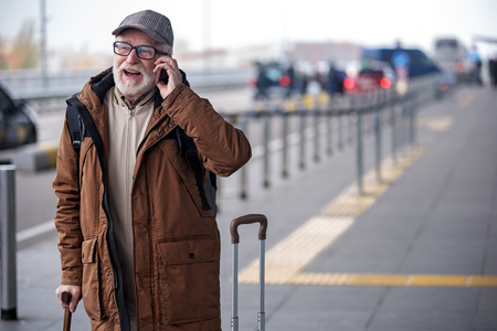 Deeply involved in conversation. Portrait of joyful senior man with beard is resting on walking stick and talking on smartphone with smile. He is standing outdoors with his suitcase. Copy space Stock Photo