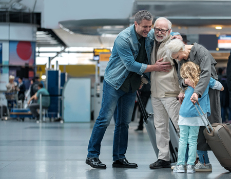Happies moment. Full length of aged father is hugging his adult sun and expressing gladness. Old joyful woman is embracing her little grandchild while standing in waiting hall at airport. Copy space