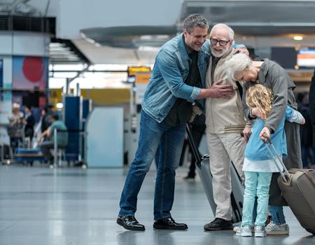 Szczęśliwa chwila. Pełnorosły wiekowy ojciec przytula swoje dorosłe słońce i wyraża radość. Stara radosna kobieta obejmuje swojego małego wnuczka stojąc w poczekalni na lotnisku. Skopiuj miejsce Zdjęcie Seryjne