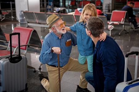 最も近い親戚。陽気な老人と彼の大人の息子のトップビューは、空港のラウンジで彼らの小さな子供を抱きしめながらしゃがんでいます。喜びでお