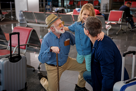 Closest relatives. Top view of cheerful aged man and his adult son are squatting while hugging their little child at airport lounge. They are feeling gladness while looking at each other with joy Stockfoto