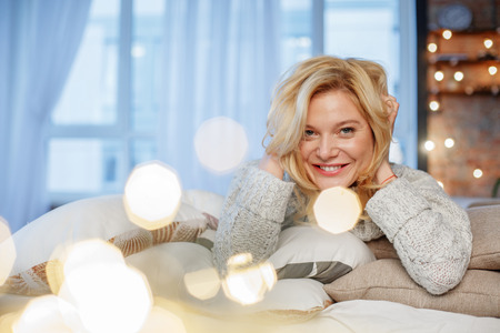 Happy woman lying on bedding and posing at camera. She is smiling and touching her hair. Copy space in left side