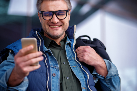 Low angle of positive middle-aged guy in glasses is standing near airport and typing message on smartphone. He is looking at screen with wide smile