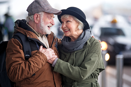 My love with you. Waist up of pleasant elderly bearded man with backpack and charming old woman are standing outdoors and hugging. They are looking at each other with fondness Stok Fotoğraf