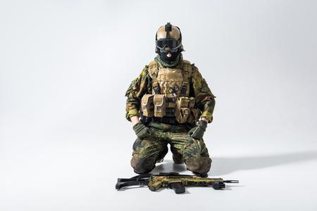 Portret van het rustige militair knielen terwijl het bekijken aanvalsgeweer. Het lokaliseren op grond. Geloof en oorlogsconcept