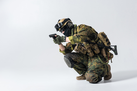 Full length portrait of serene peacemaker in helmet and balaclava firing pistol. Military concept. Copy space