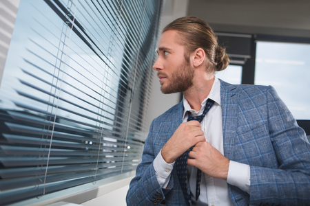 Waist up profile of well dressed man tying a cravat and peeking at the office blinds. His face is looking tranquil Stock Photo