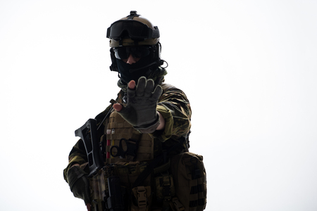 Portrait of serious defender in ammunition pointing by palm of hand in camera. Protection concept. Isolated and copy space