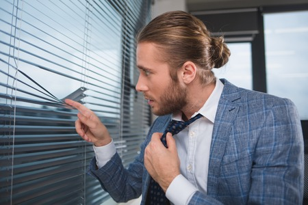 Profile of attentive boss spying on the office window. He is holding tie with his hand