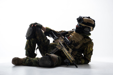 Full length side view calm soldier having rest. He keeping assault rifle in arms. Relax and work concept