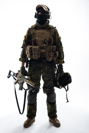 Full length portrait of serious peacemaker holding helmet and modern weapon in arms. Army concept Stock Photo