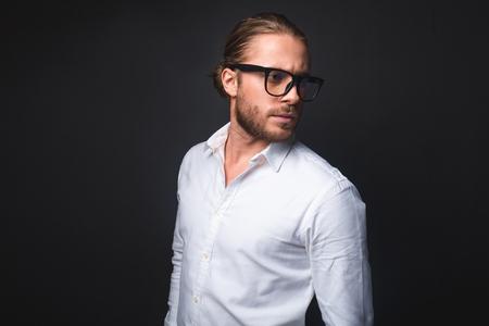 スタイリッシュな男nメガネのウエストアップ。彼は気楽に見える。黒い背景に隔離されています。左側の領域をコピーする