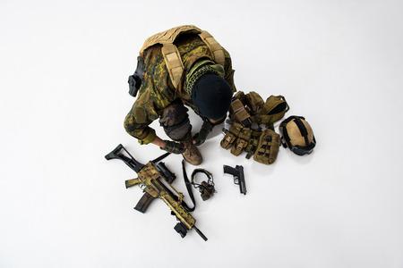 Top view defender tying shoelaces on footwear while preparing army uniform. Arrangement concept
