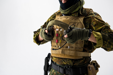 Close up arms of defender holding headset. He wearing bulletproof vest. Army concept. Isolated and copy space