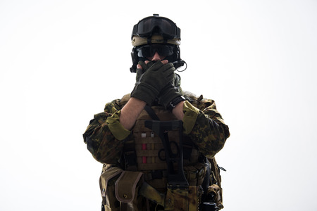 Portrait of serious soldier closing mouth by hands while wearing military uniform. Confidence concept. Isolated