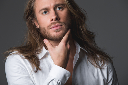 Portrait of attractive young man holding his goatee and looking at camera with tranquility. Isolated on grey background