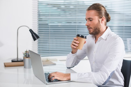 Time to relax. Side view profile of intelligent male sitting in the office. He is holding cup of drink and using notebook Фото со стока