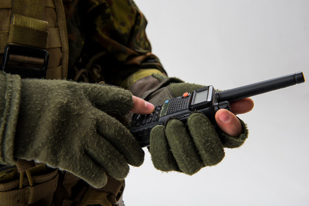 Close up soldier hand holding modern radio set. He typing in it. Digital device and army concept