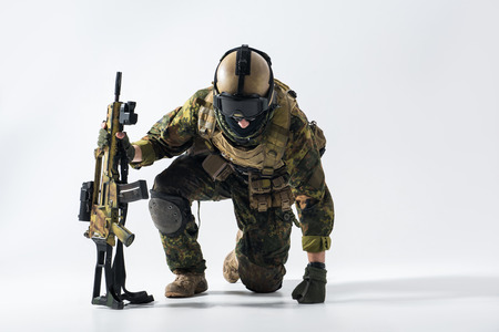 Portrait of stern defender rising from knees while leaning on weapon. Profession concept