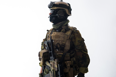 Side view serene peacemaker speaking by digital device while keeping assault rifle. Military and communication concept. Isolated