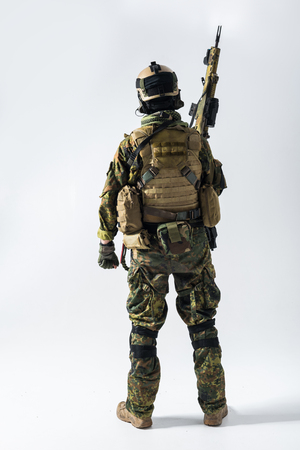 Full length peacemaker rising hand with assault rifle up while turning back to camera. Army concept