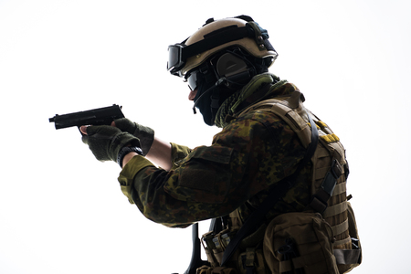 Side view serious defender wearing in ammunition firing with gun. Protection concept. Isolated