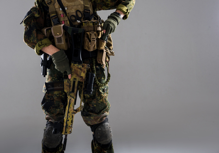 Close up man arm in generic military uniform holding modern weapon. Technology and military concept. Copy space and isolated 版權商用圖片