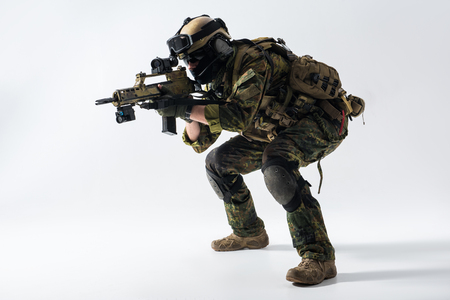 Side view full length concentrated soldier shooting with assault carbine at war. Protection concept