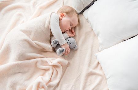 Vue de dessus de bébé paisible allongé sur les draps et suçant son doigt. Elle dort avec un ours en peluche dans une étreinte