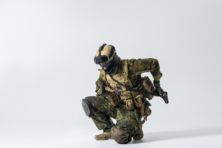 Full length portrait of serious soldier shooting with gun while taking assault rifle. War concept. Copy space
