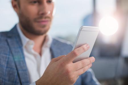 Medios de comunicación. Ciérrese para arriba del hombre sin afeitar que sostiene el teléfono móvil. Centrarse en el teléfono móvil Foto de archivo