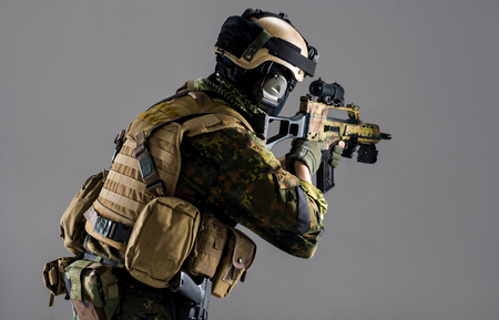 Side view serious male pointing assault carbine while wearing ammunition. Army concept Foto de archivo