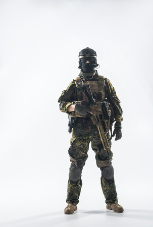Full length portrait of calm peacemaker wearing military ammunition and holding modern weapon in hands. Defense concept Stock Photo