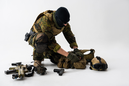 Soldier kneeling and putting ammunition. Assault rifle, gun and helmet locating near him. Military concept Stock Photo