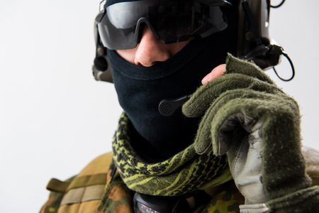 Serene peacemaker in balaclava speaking by digital device. Army and conversation concept. Close up portrait