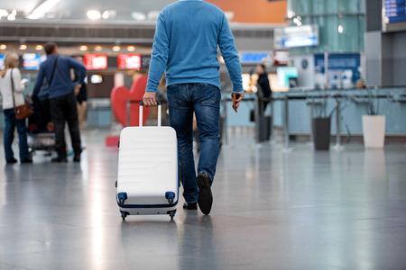 Altijd in beweging. De achtermening van de zekere mens in vrijetijdskleding loopt langs luchthavenzitkamer terwijl het dragen van zijn bagage. Mensen op de achtergrond