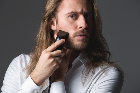 Looking good. Portrait of longhaired guy shaving his beard with shaver, looking concentrated. Isolated on grey background
