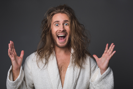 Wow. Portrait of amazed shaggy guy with opened mouth lifting his hands up. Isolated on grey background