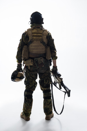 Full length soldier keeping modern weapon while turning back to camera. Army concept