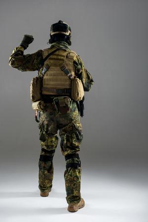 Full length man wearing ammunition while flourishing arm. He turning back to camera. Military concept Stock Photo